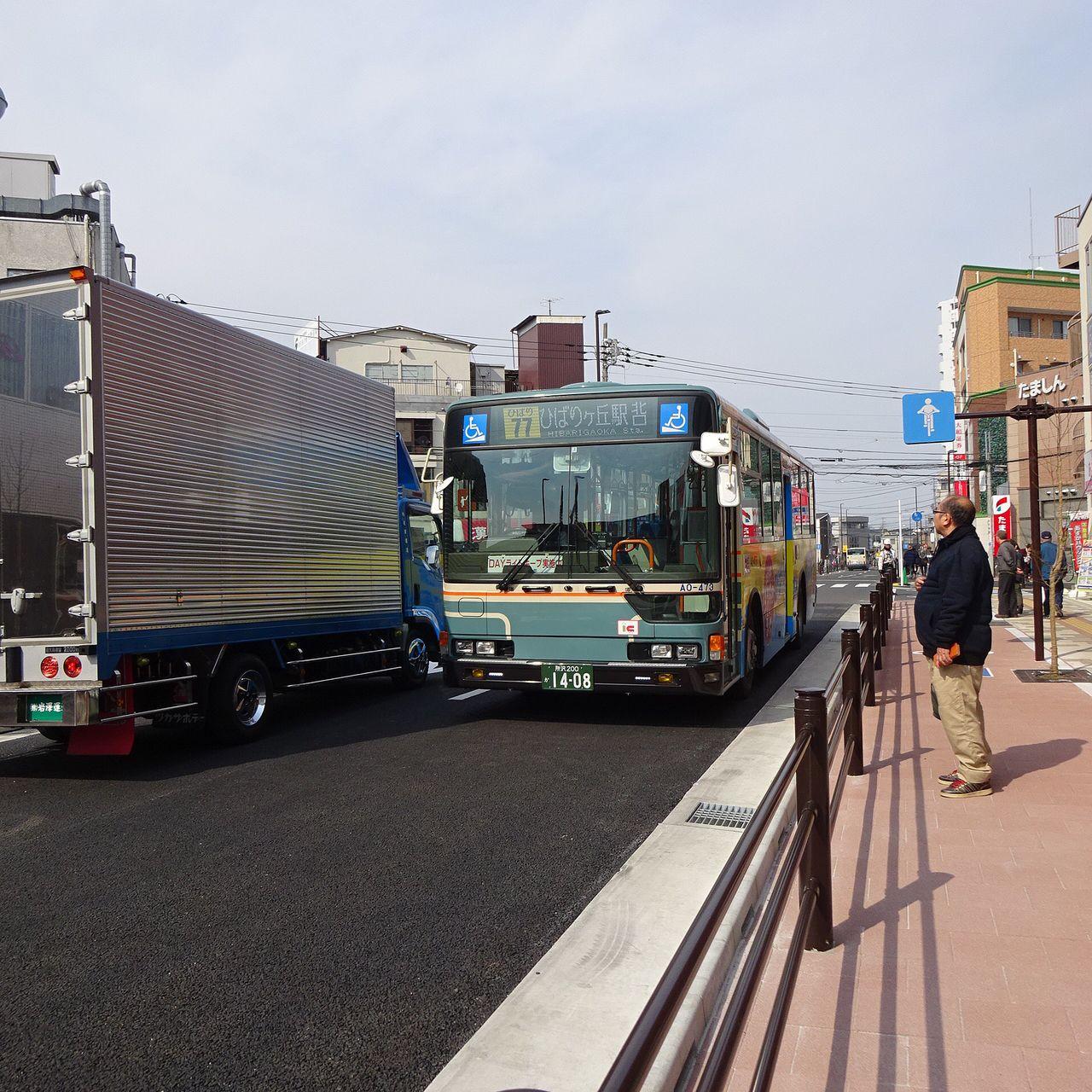 閉鎖後のバス乗場の前を通過するバス