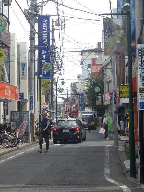 北口メイン通り、人、車、自転車がすれ違う