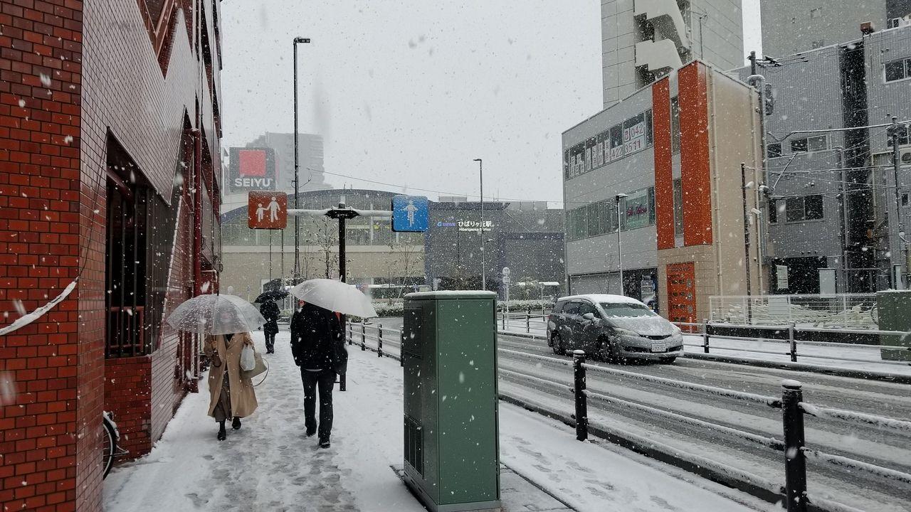 傘をさしながら駅へ向かう人たち